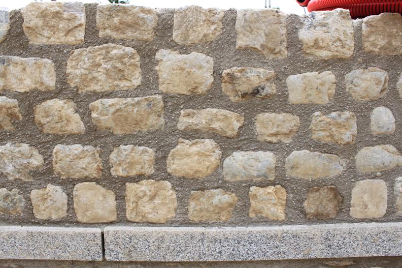 Parapet en pierre de pavage avec la finition joints brossés et plinthe en granit.